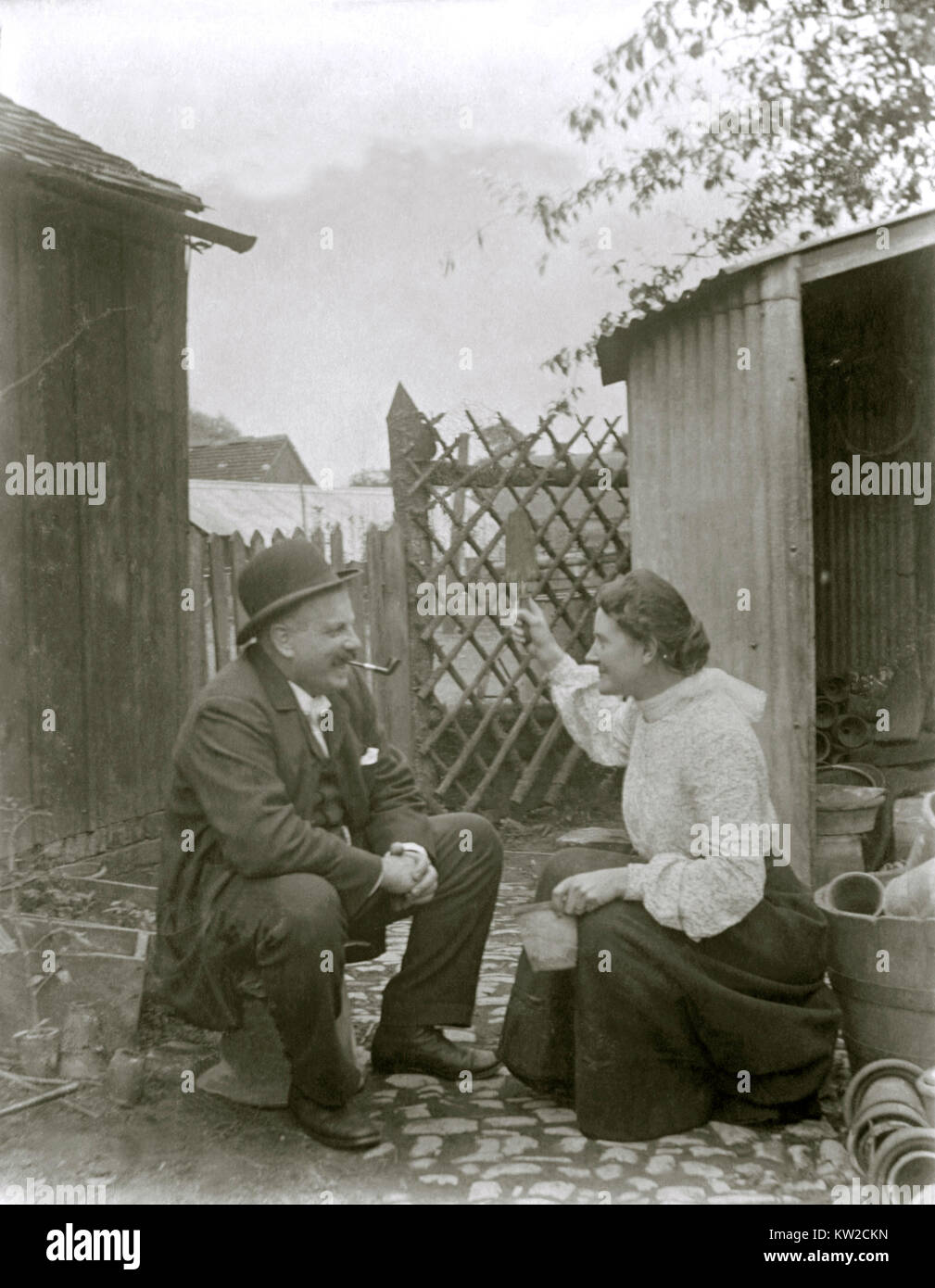Victorian woman and man share a joke behind the potting shed (c. 1900) - however she seems to threatening him with - Stock Image