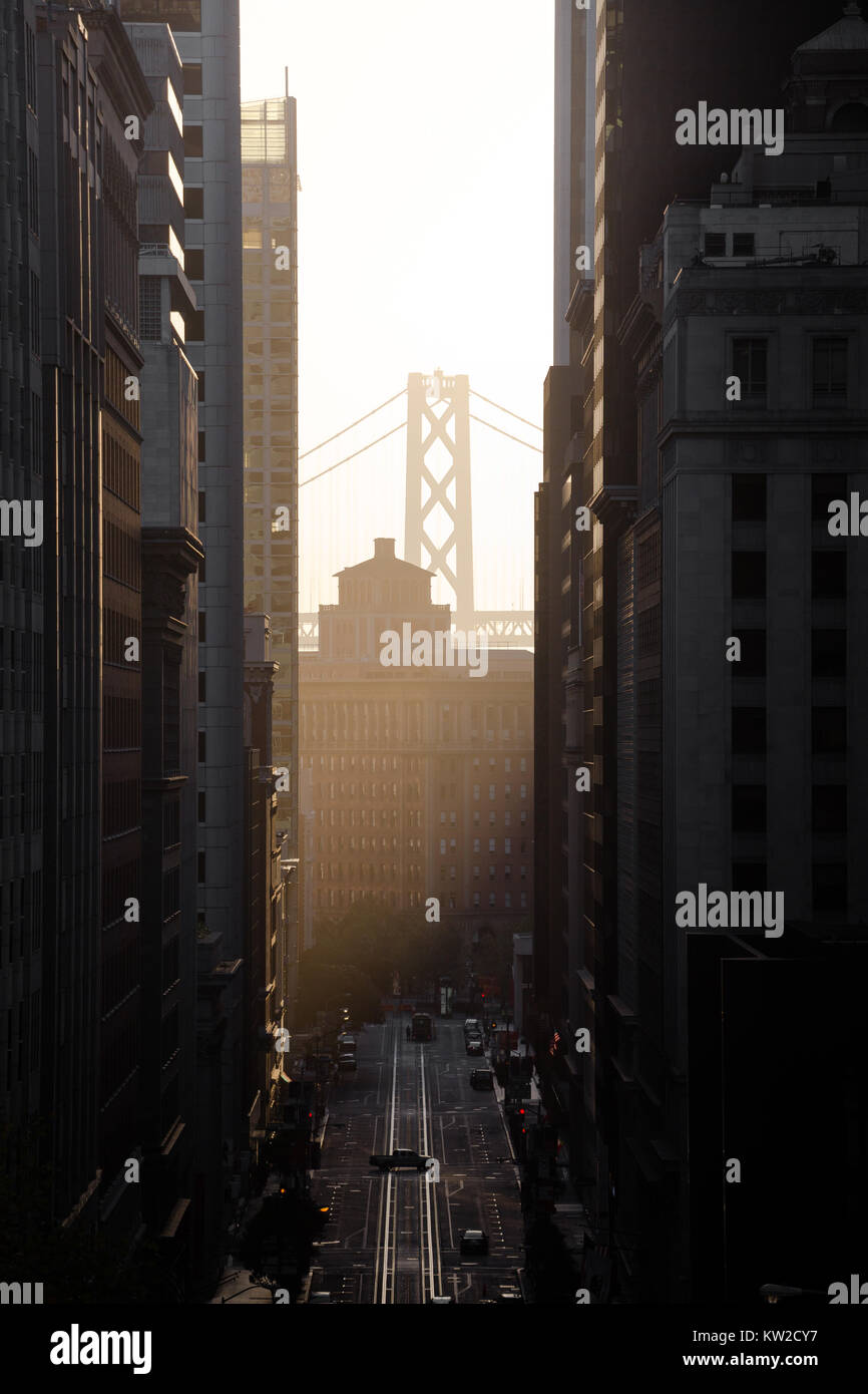 Classic view of historic California Street with famous Oakland Bay Bridge illuminated in first golden morning light - Stock Image