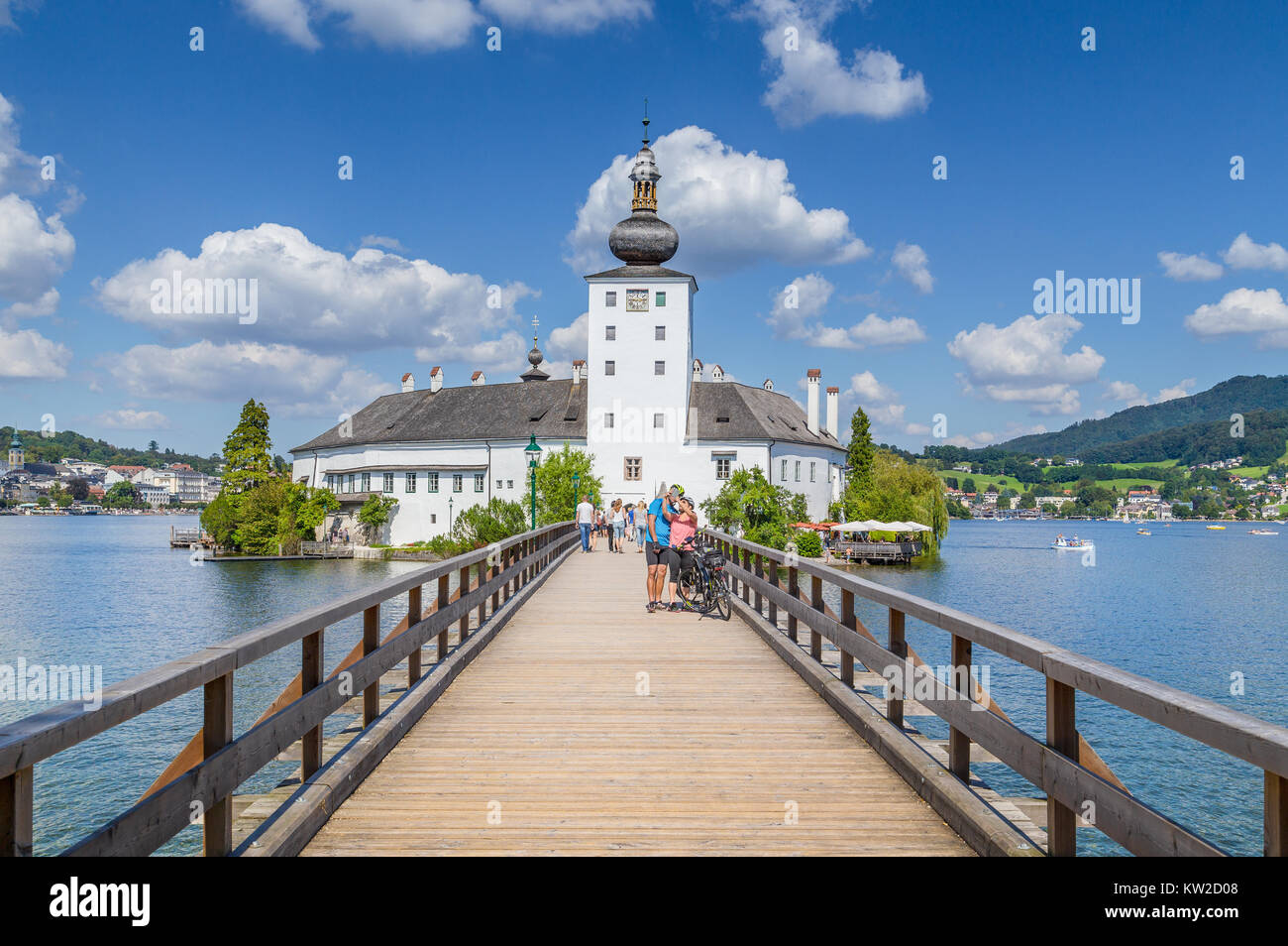 Tourist couple taking a selfie in front of famous Schloss Ort on a sunny day with blue sky and clouds in Gmunden, - Stock Image
