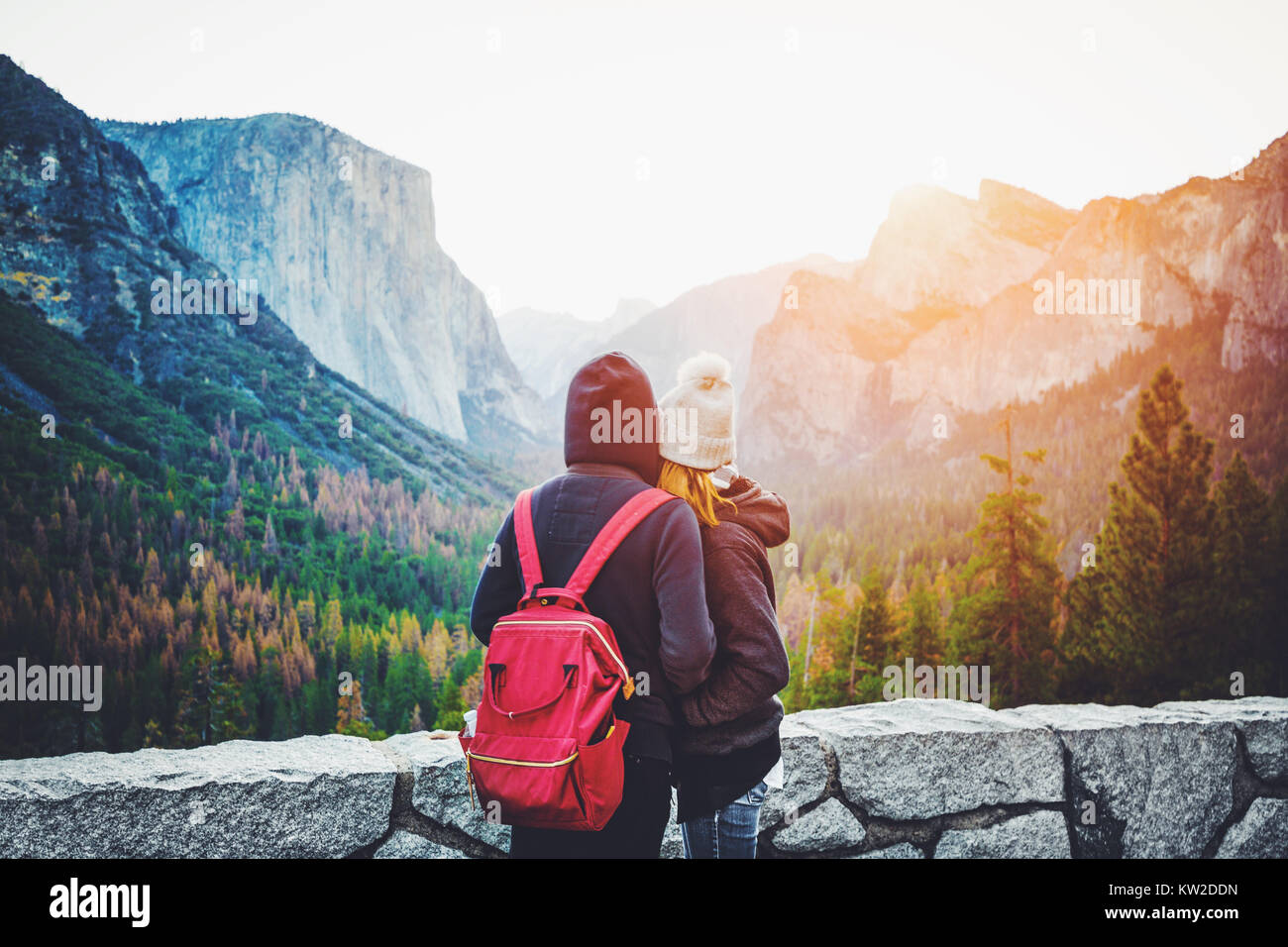Romantic view of a young couple enjoying famous Tunnel View in beautiful golden morning light at sunrise in Yosemite - Stock Image