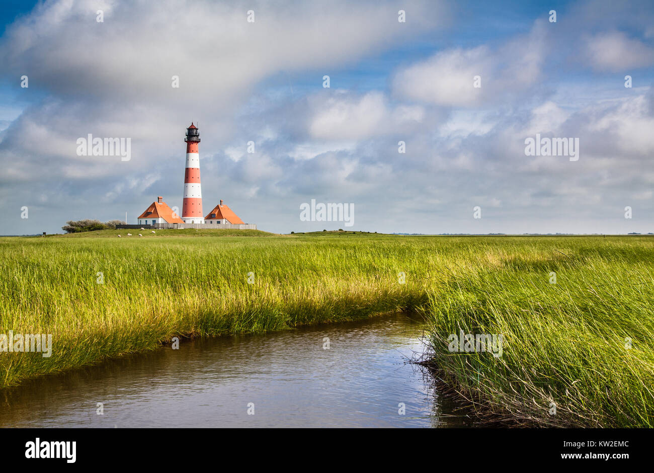 Beautiful view of landscape with small pond and lighthouse in the background at North Sea in Nordfriesland, Schleswig - Stock Image