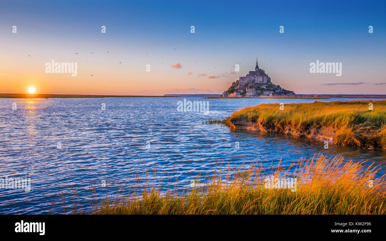 Panoramic view of famous Le Mont Saint Michel tidal island in beautiful golden evening light at sunset in summer, - Stock Image