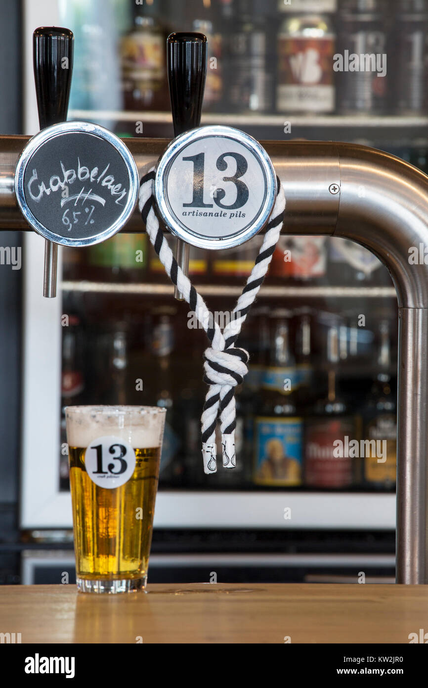 Hangman's rope, symbol of the city Ghent around tap and beer glass with pilsner / pilsener / pils 13, Belgian - Stock Image