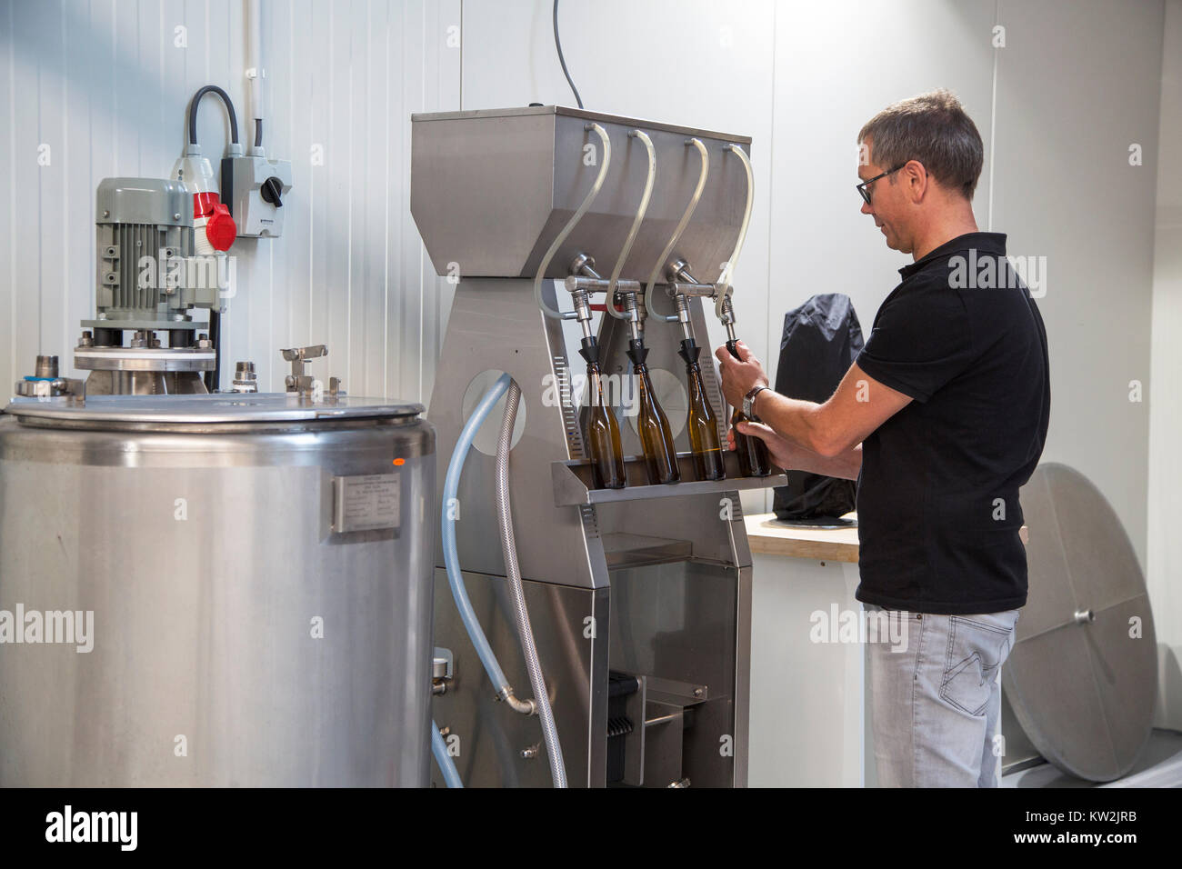 Brewer bottling beer by filling beer bottles with filler / filling machine in local brewery - Stock Image