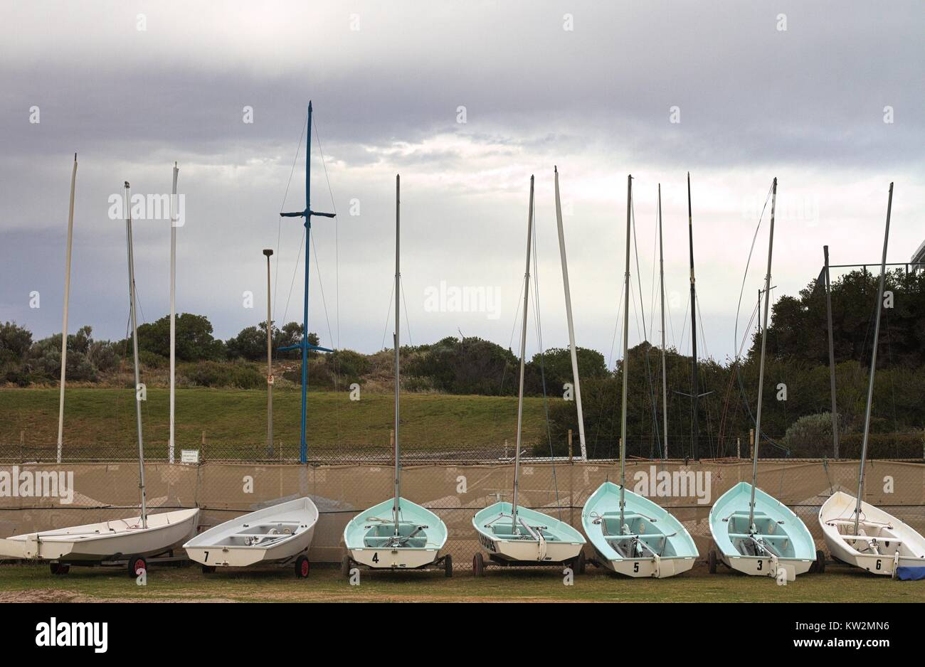 Sven small sailboats lined up in a boatyard, facing inland with grey cloudy sky. Stock Photo