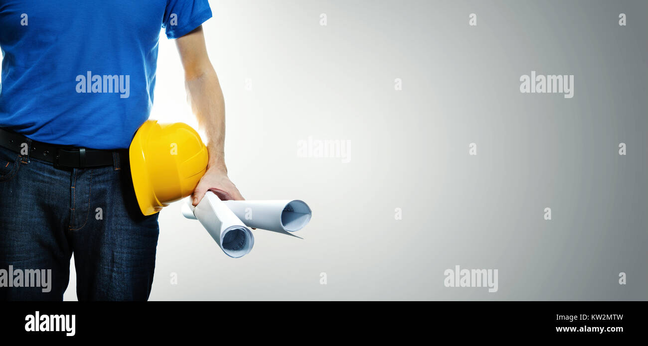 construction engineer with blueprint rolls in hand on gray background with copy space - Stock Image