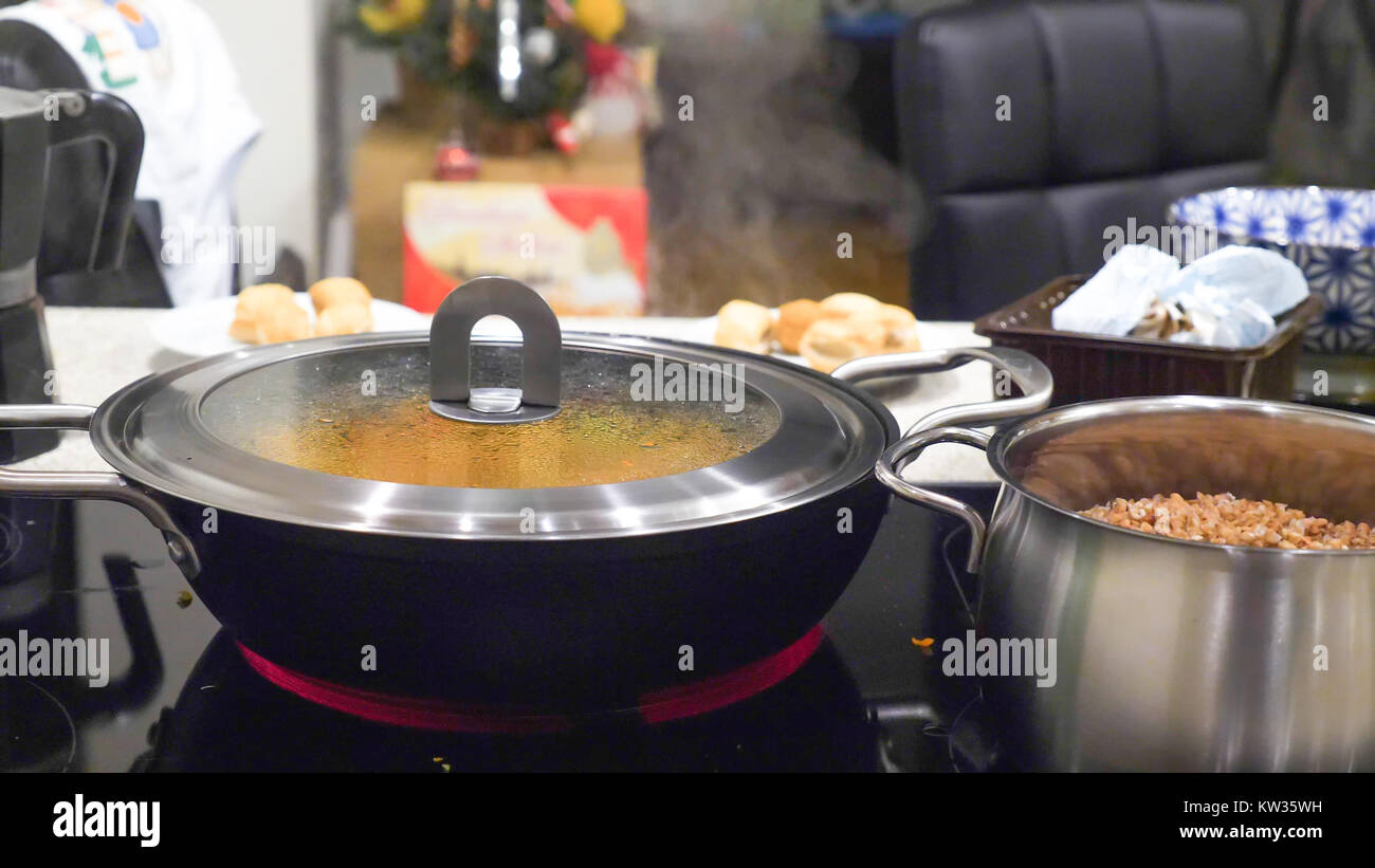 Fresh vegetable stew frying in pan casserole on modern electric cooker. - Stock Image