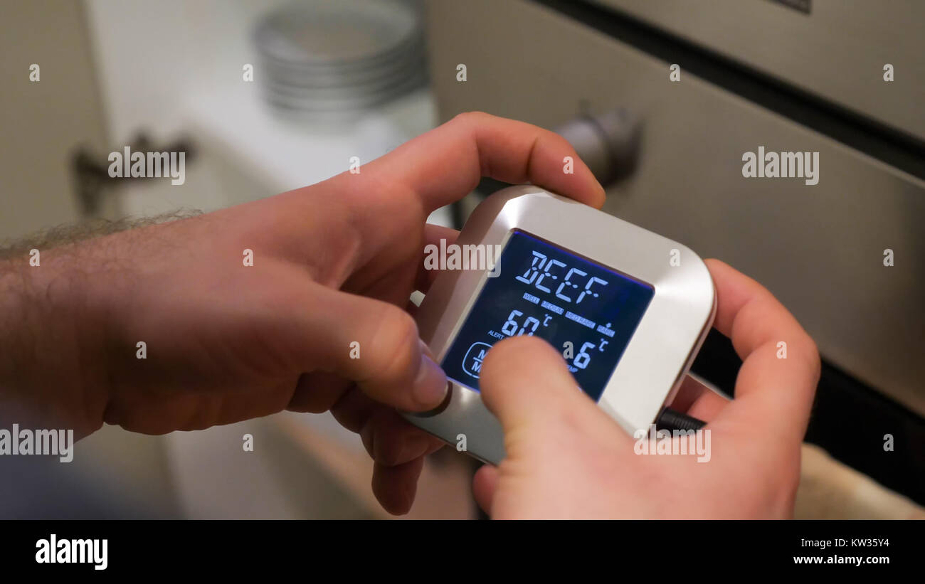 Male hands set up temperature control unit for roasting beef meat in oven. - Stock Image