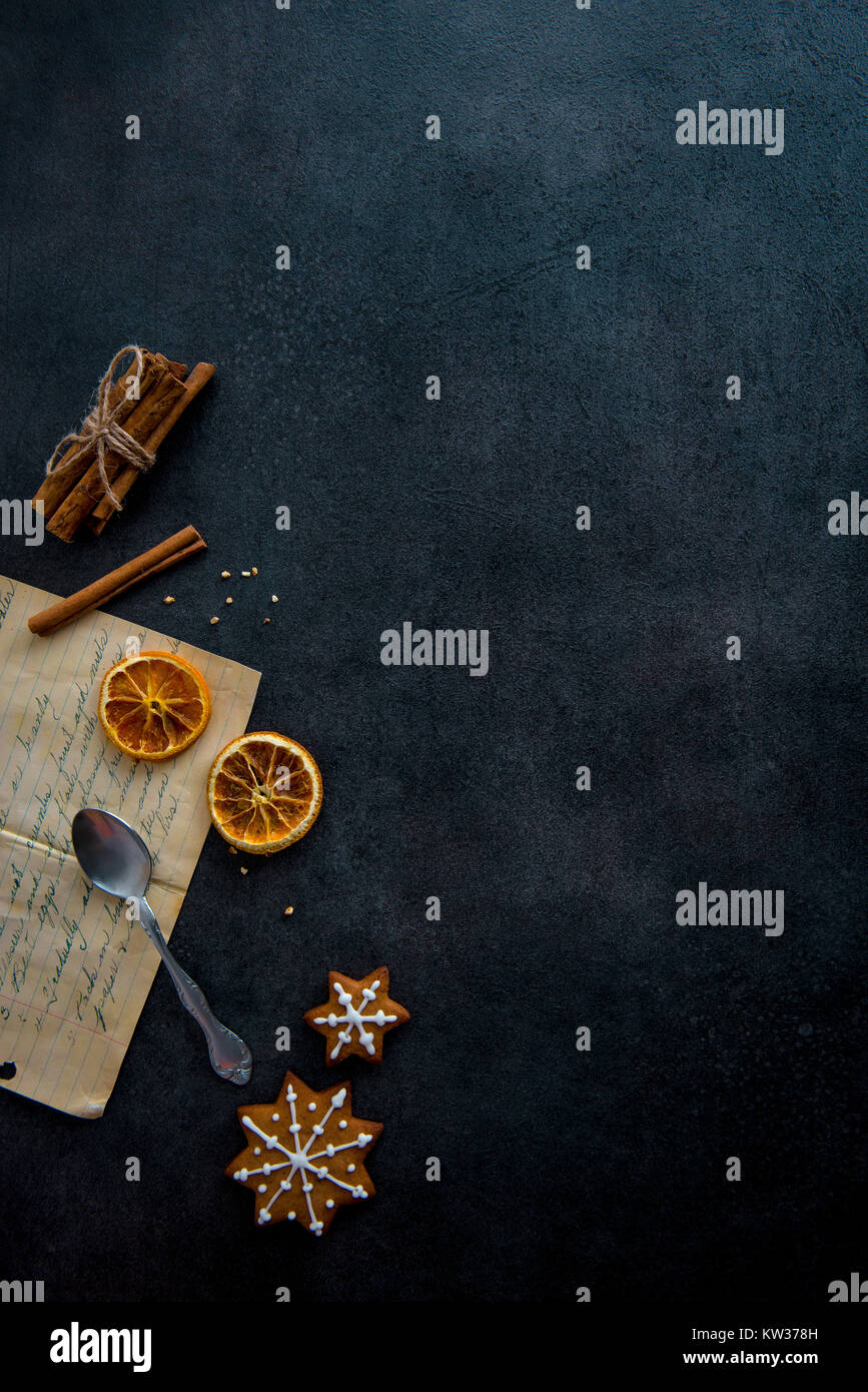 Food preparation. Old recipe and some ingredients (cinnamon sticks, dried orange slices) with two star shaped gingerbread - Stock Image