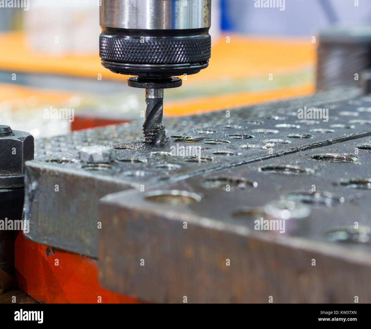 Tapping tool in spindle tapping into a hole in steel plate - Stock Image
