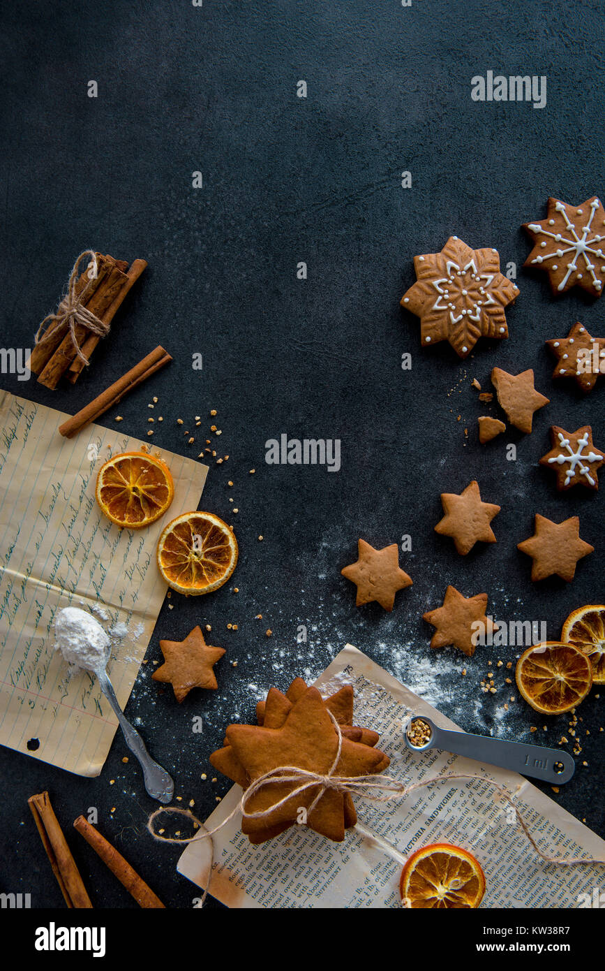 Top view of food preparation. Star shaped gingerbread cookies with icing and ingredients (cinnamon sticks, dried - Stock Image