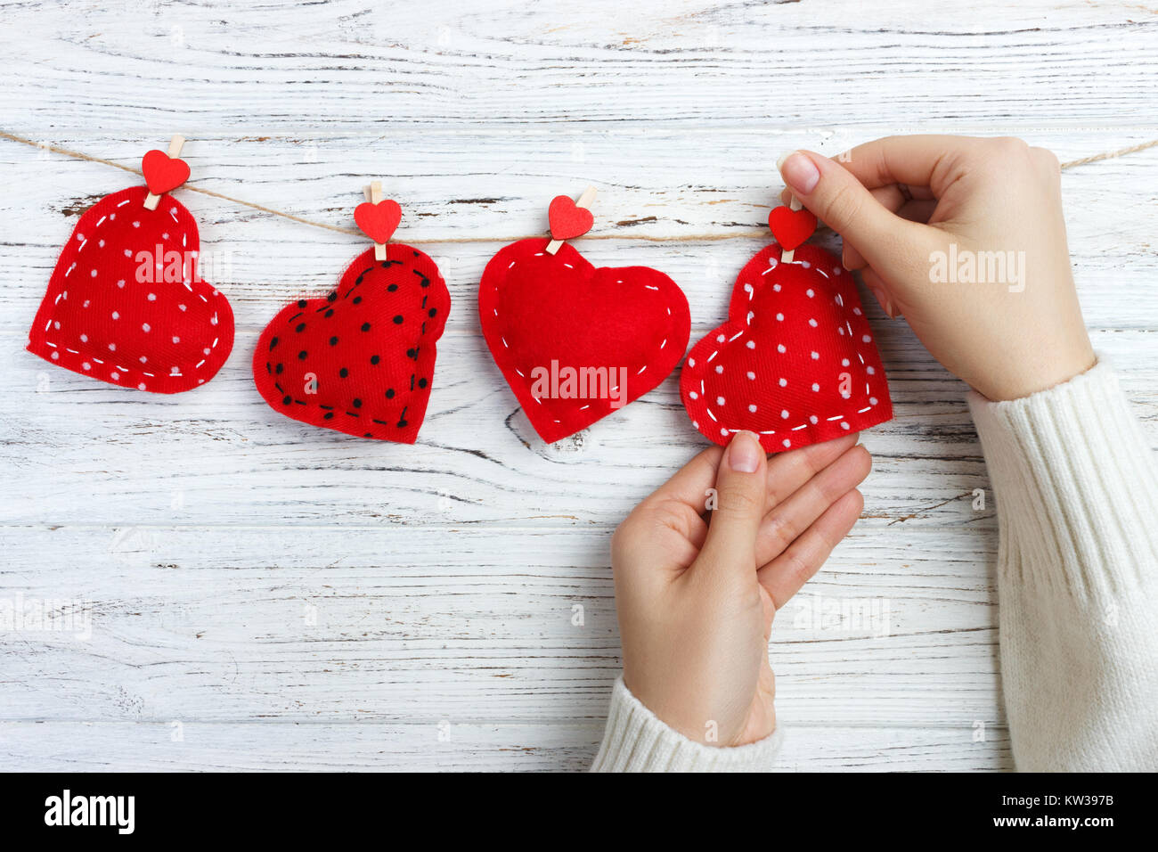 girl hanging hearts on a rope. wooden background. - Stock Image