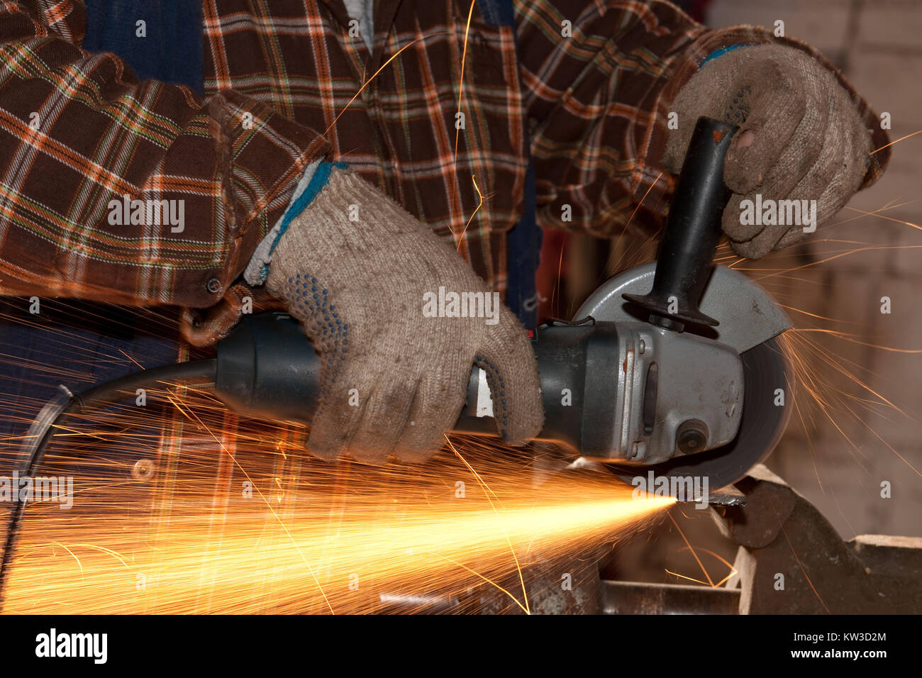 Blue collar worker working with an angle grinder - Stock Image