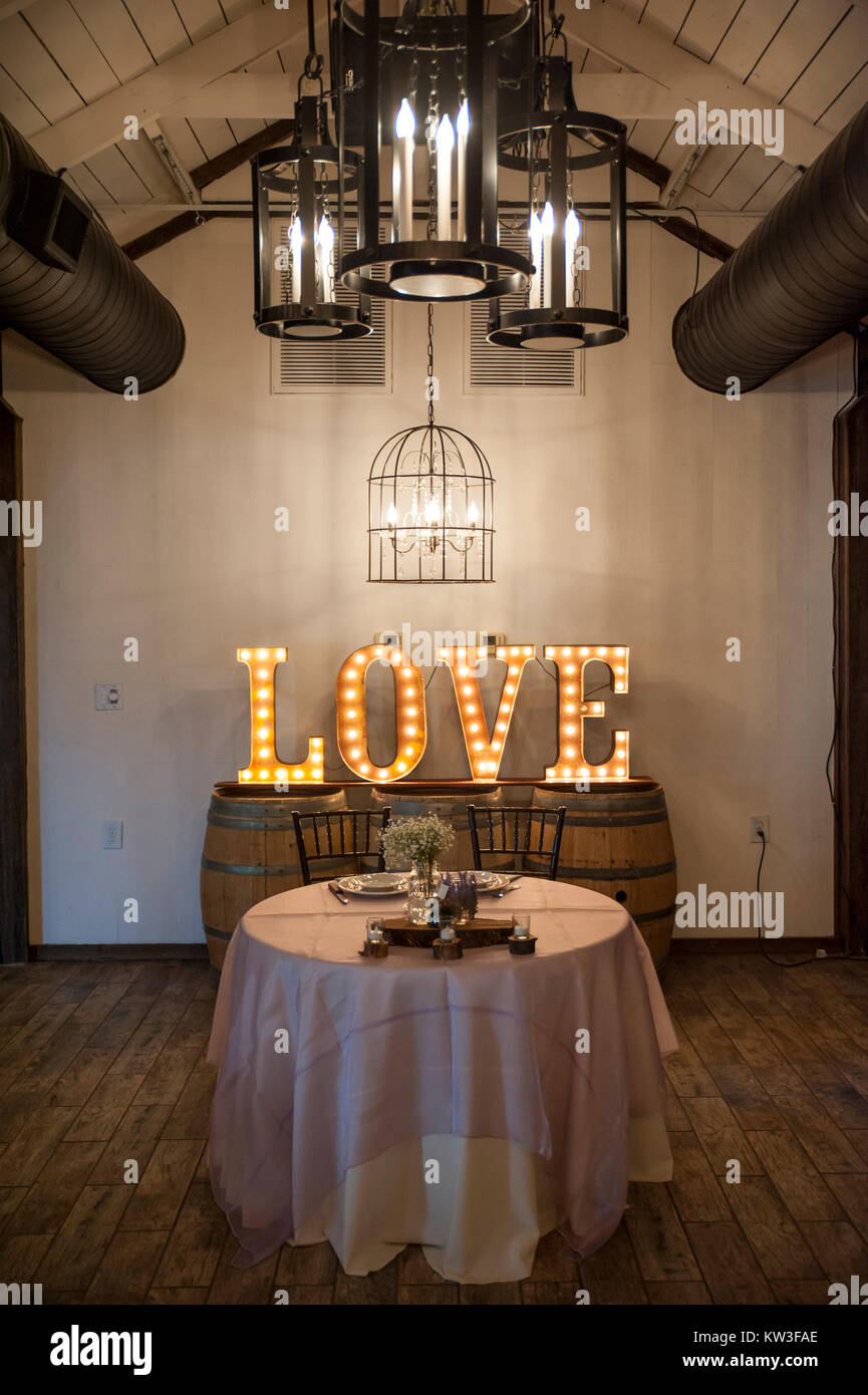 The head table (for bride and groom) in a reception hall - includes sign that says 'Love', spelled out with - Stock Image
