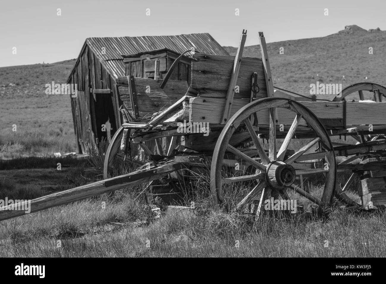 A black and white shot of an old wagon and an outhouse, with hills and shrubs, in the historic town, Bodie - Stock Image