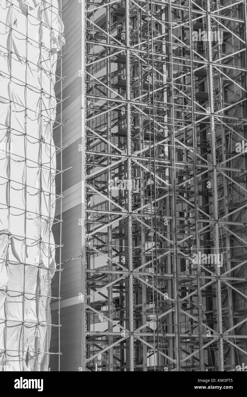 A black and white, isolated shot of a building under construction, partly covered and partly exposed - Stock Image