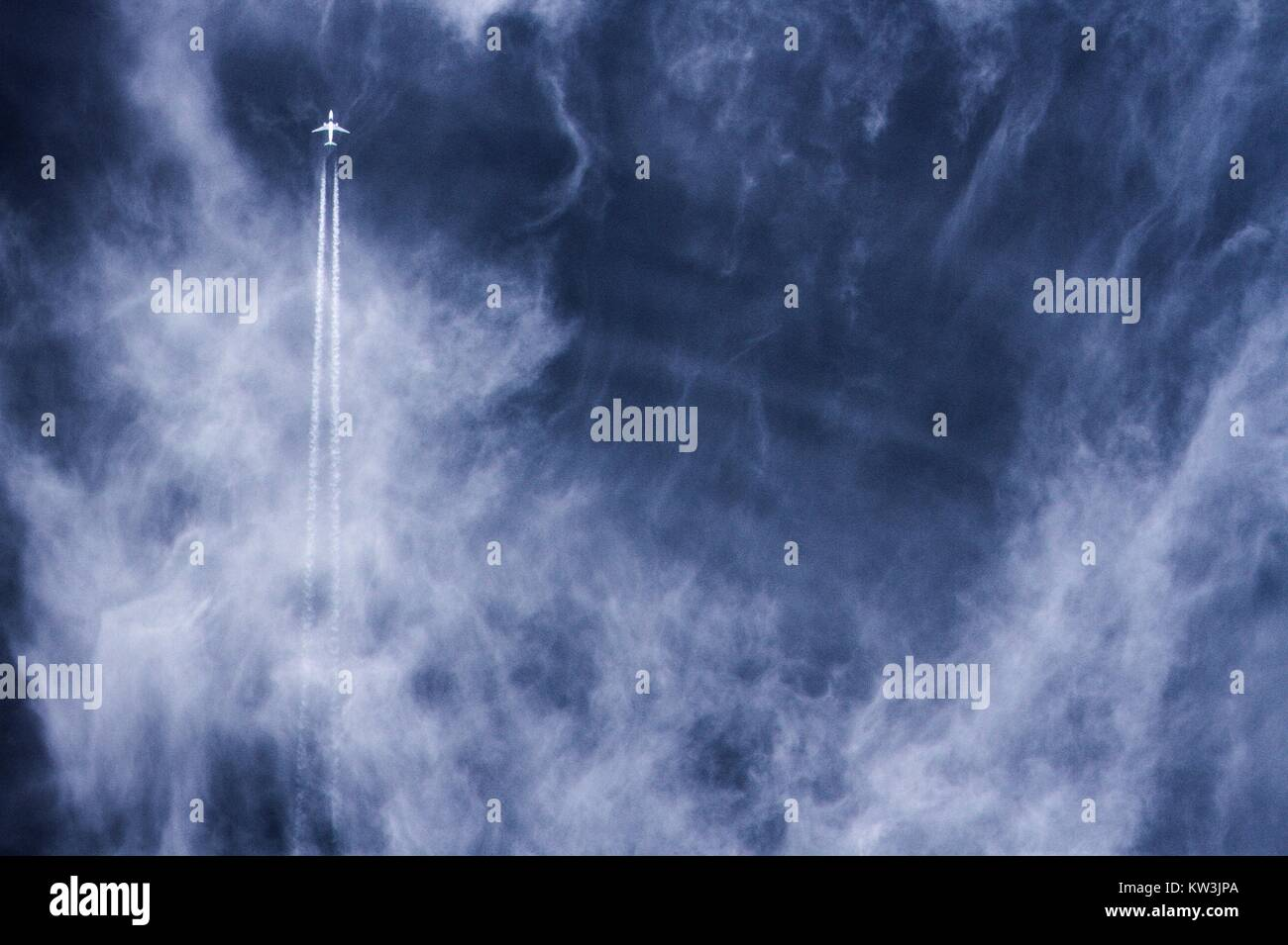 Far away jet plane travelling straight up with vapor trails against blue cloudy sky. Stock Photo