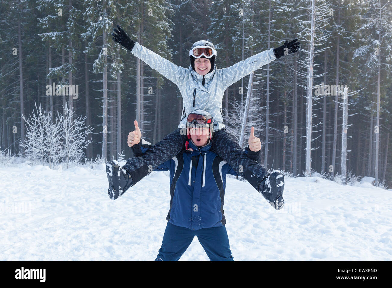 Young man holding his girlfriend on his shoulders. Girl embraces guy for neck. girl and guy in ski suits on vacation - Stock Image