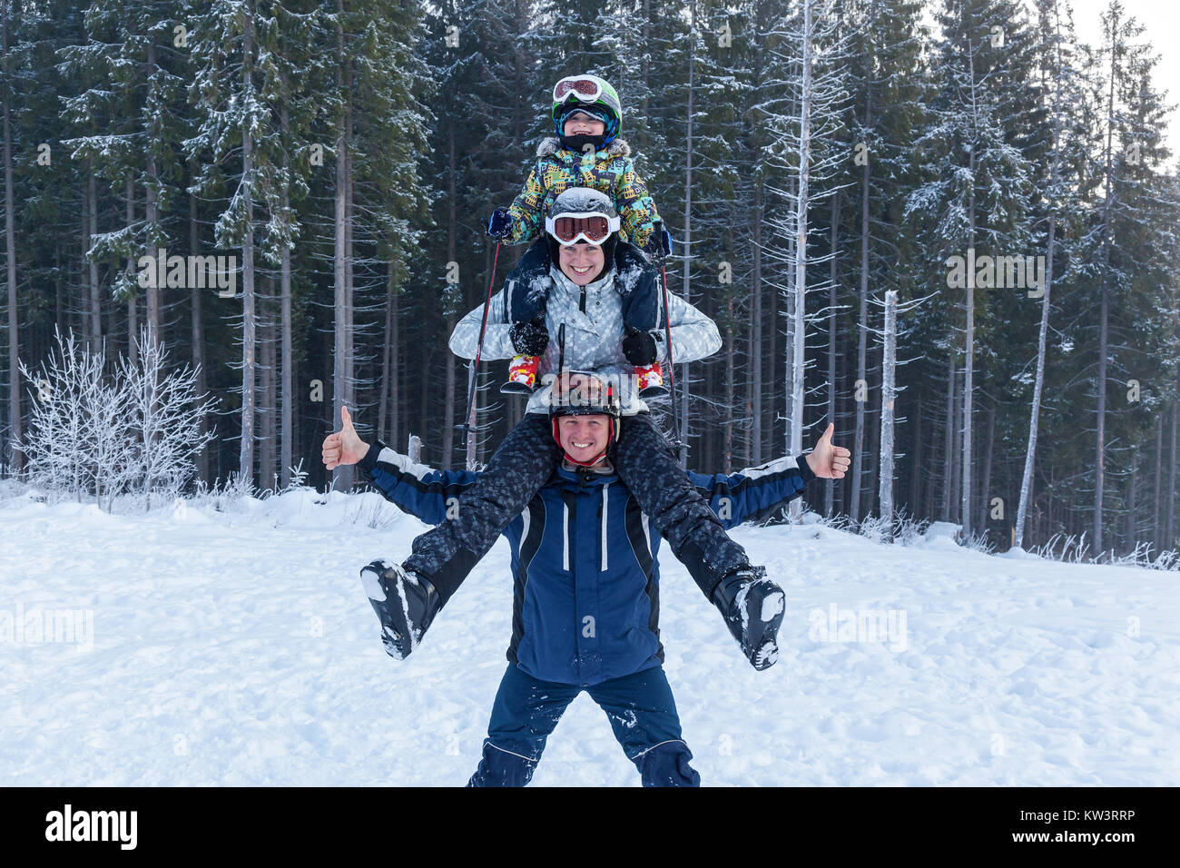 pyramid father mother and child in ski suits on vacation. Young man holding his girlfriend on his shoulders. Girl - Stock Image