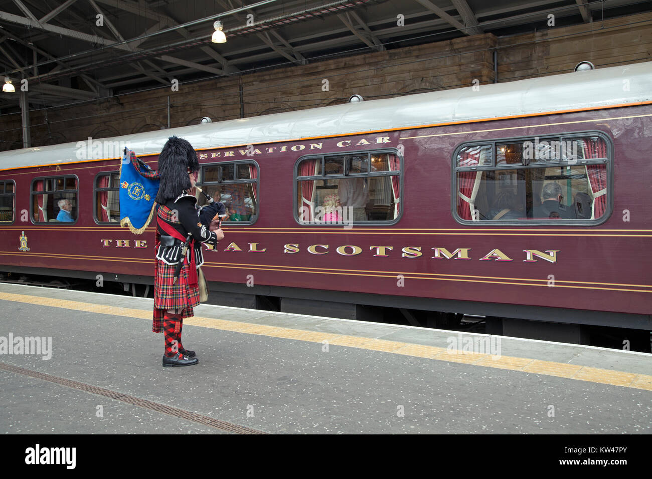 A piper greeting The Royal Scotsman train in Edinburgh Waverley train station, Scotland. - Stock Image