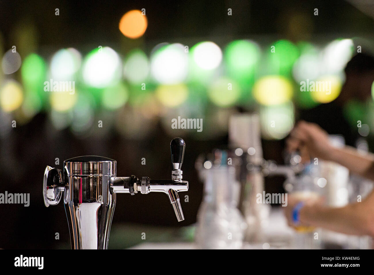 Dispensing draft beer in a bar from beer dispenser - Stock Image