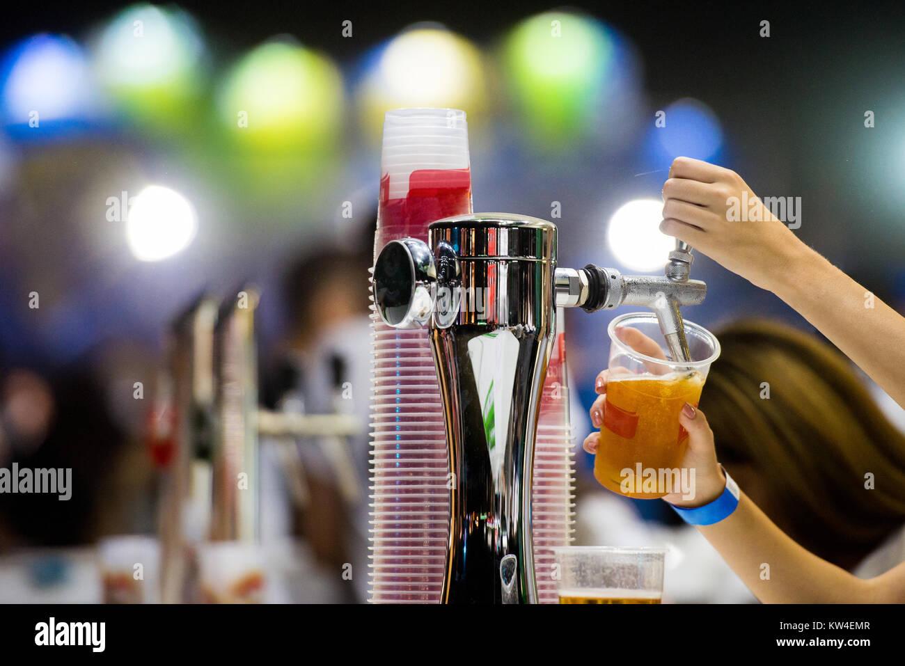 Bartender dispensing draft beer in a bar from beer dispenser - Stock Image