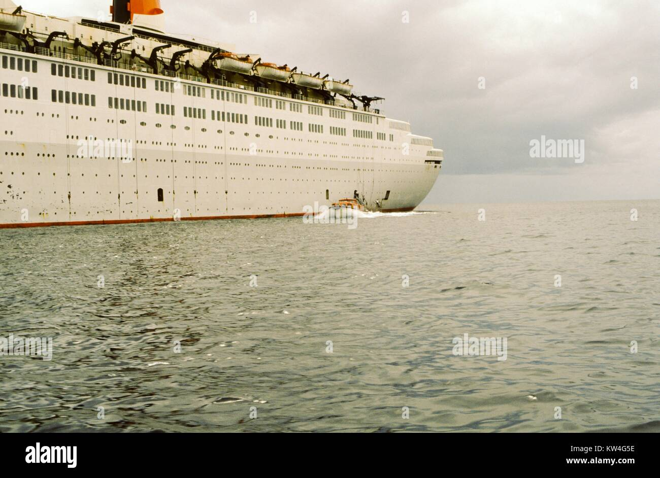 Aft portion of the Cunard Line's Queen Elizabeth 2 cruise ship, with a small motor yacht approaching, at sea, 1975. Stock Photo