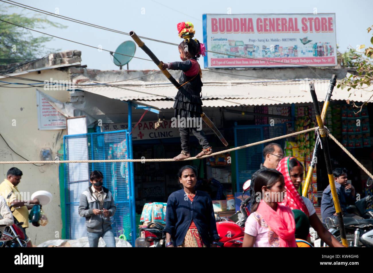 India. Bihar. Bodhgaya. A small girl performs on a tightrope. - Stock Image