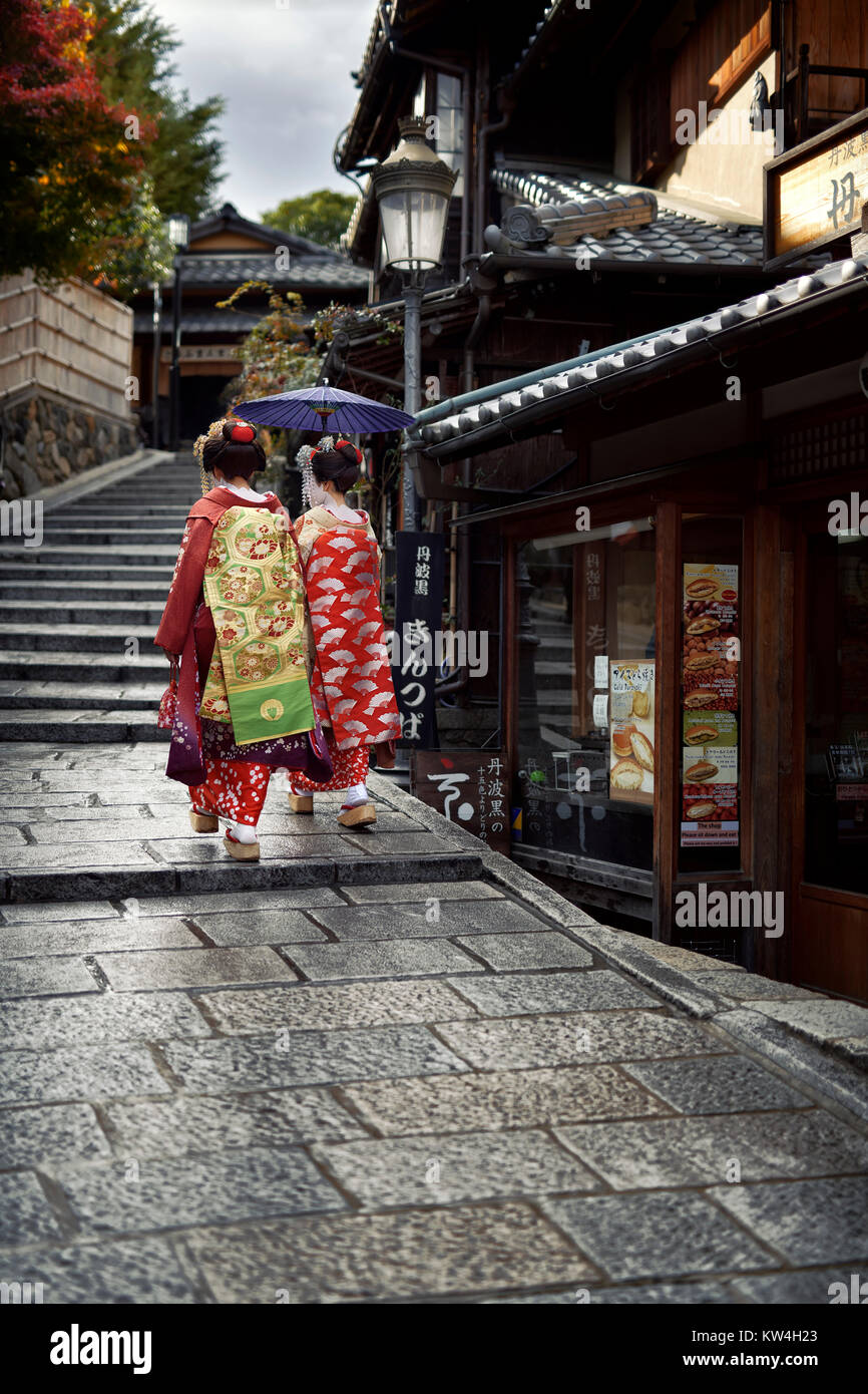 Two Maiko, Geisha apprentices in beautiful colorful kimono with long intricate obi walking with a parasol on an - Stock Image