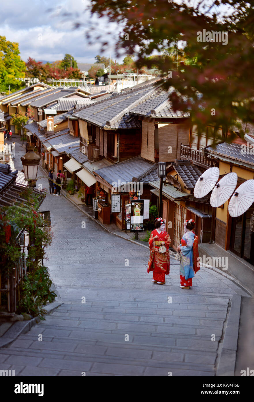 Two Maiko, Geisha apprentices in colorful kimono standing on an old street Yasaka dori in Kyoto, near Kiyomizu-dera - Stock Image