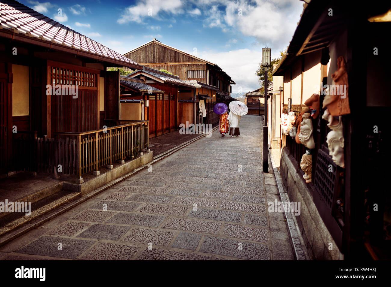 Couple with Japanese parasols wearing traditional kimono walking down an old street, Yasaka dori, near Kiyomizu - Stock Image