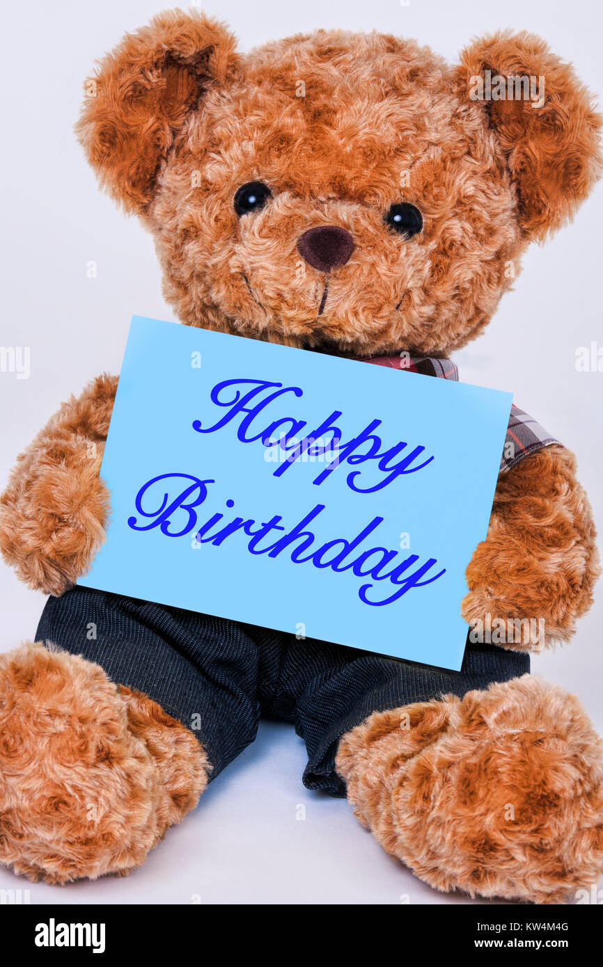 Cute teddy bear holding a blue sign that reads Happy Birthday isolated on a white background - Stock Image