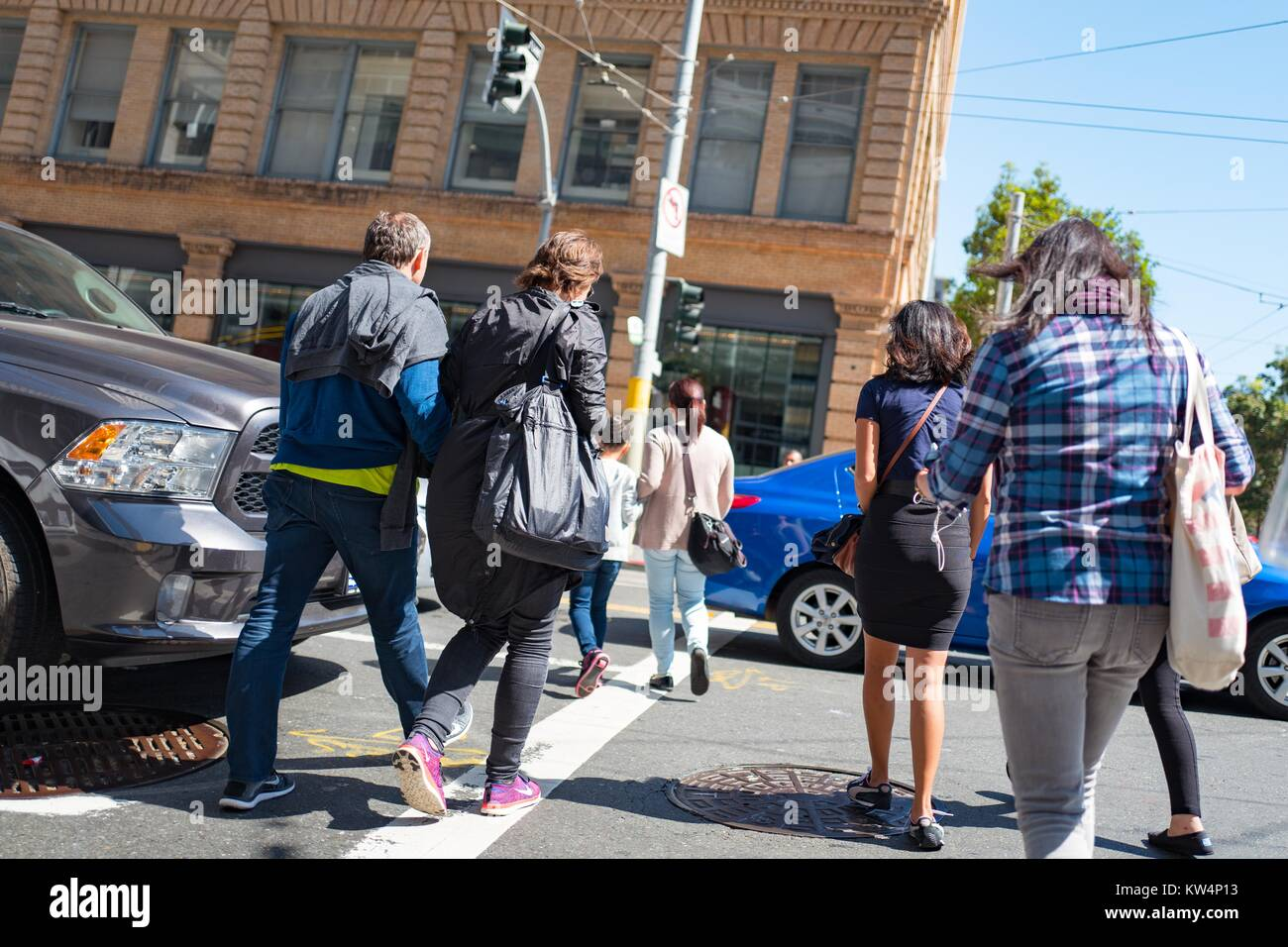 A group of people walk between cars to cross an intersection in San Francisco, California, September 4, 2016. - Stock Image