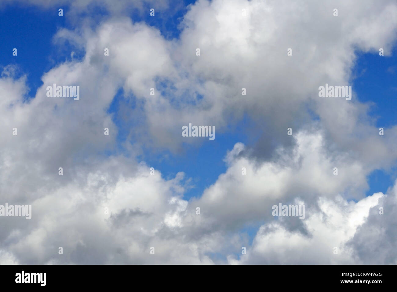 White fluffy clouds in a bright blue sky - Stock Image