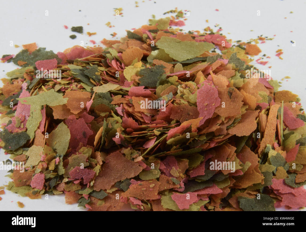A pile of fish food flakes for tropical fish - Stock Image