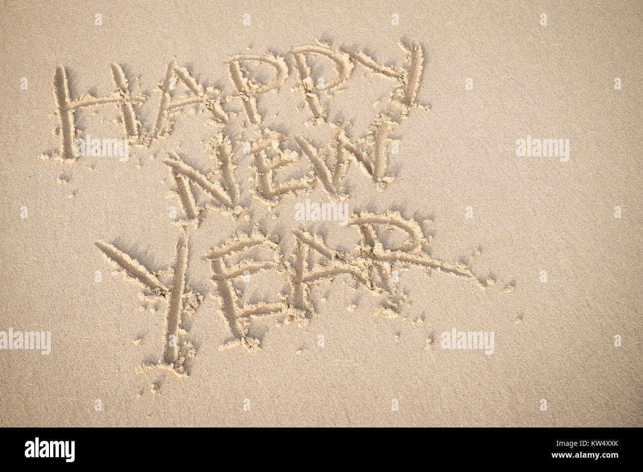 Happy New Year message handwritten on smooth sand beach - Stock Image