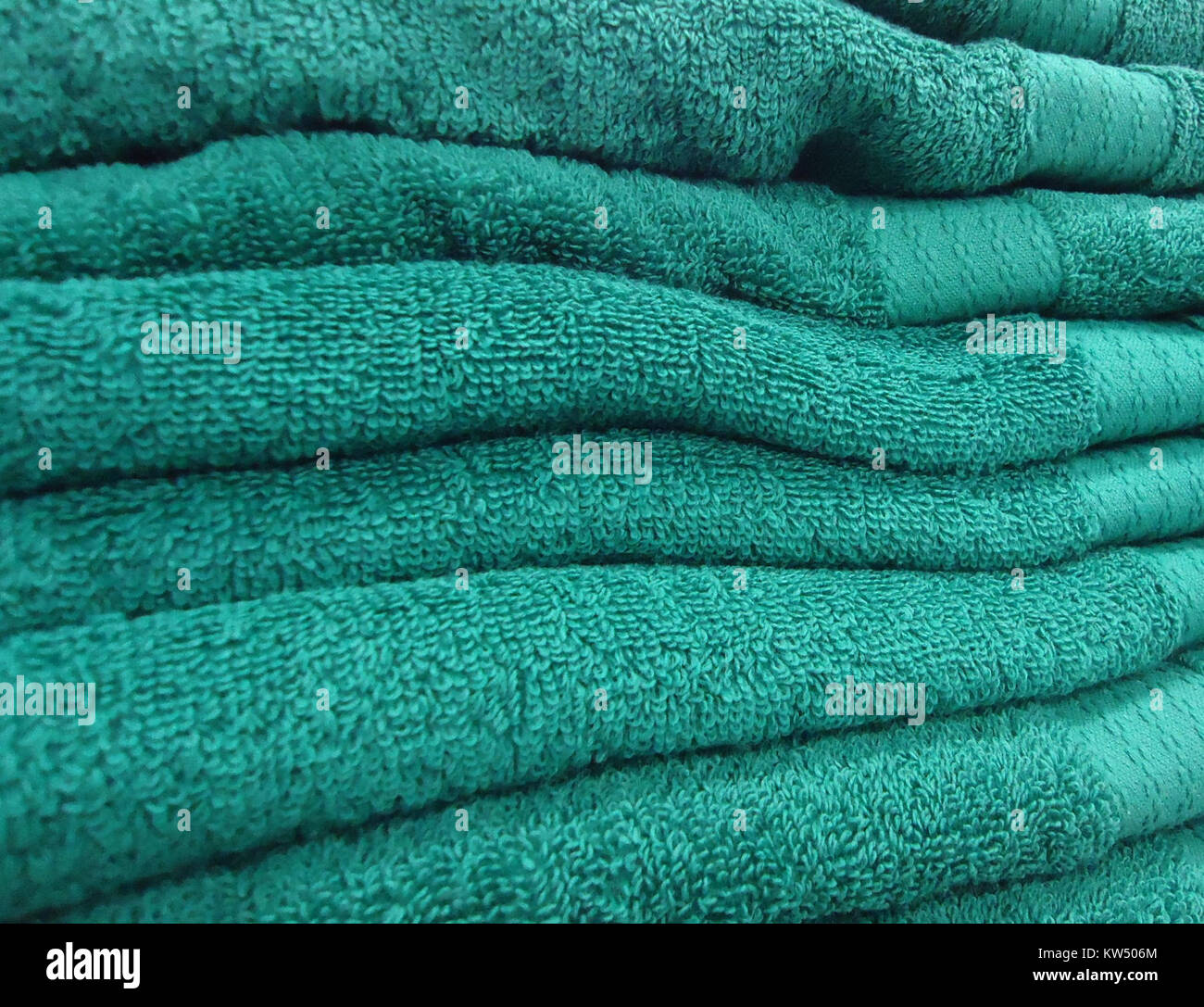 Bluegreen towels in a store - Stock Image