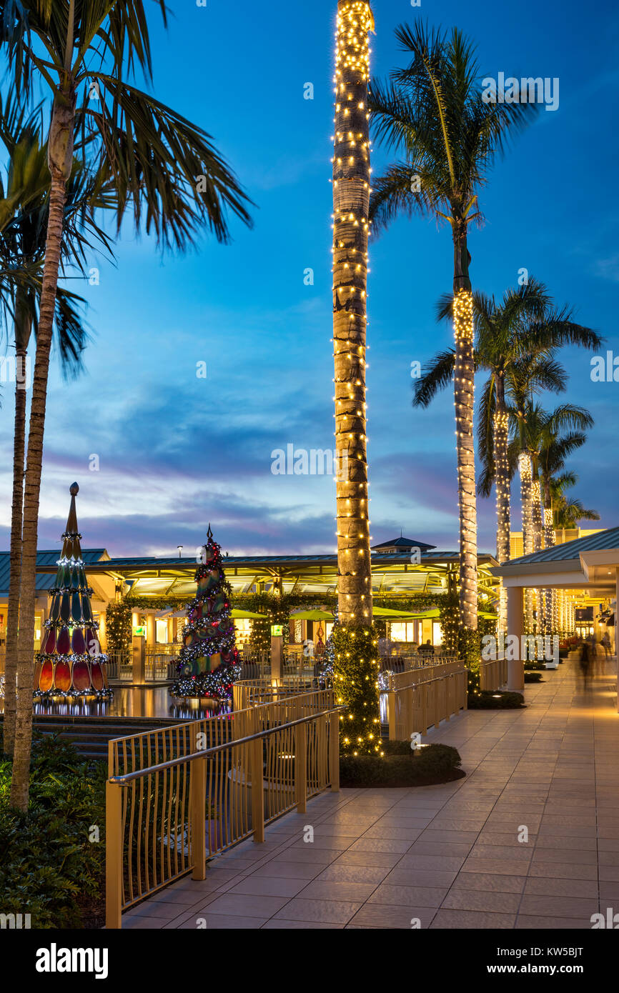 Christmas decorations and colorful sunset at the Waterside Shops - an upscale open-air mall, Naples, Florida - Stock Image