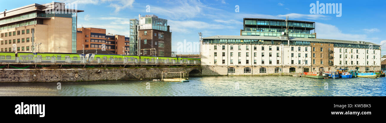 Refurbished part of Dublin Docklands or Silicon Docks on a bright morning with longboats mooded in annex of Grand - Stock Image