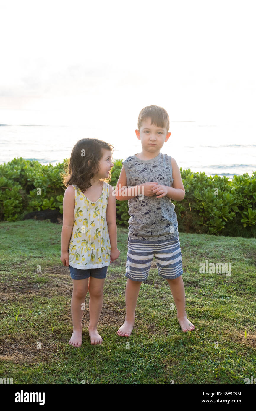 Siblings being silly together and making faces on some grass near a beach in Hawaii at sunrise. - Stock Image