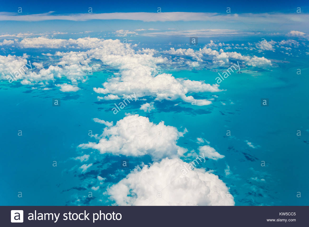 An aerial view above the clouds over the turquoise waters of the Caribbean Sea, near the Bahamas. - Stock Image