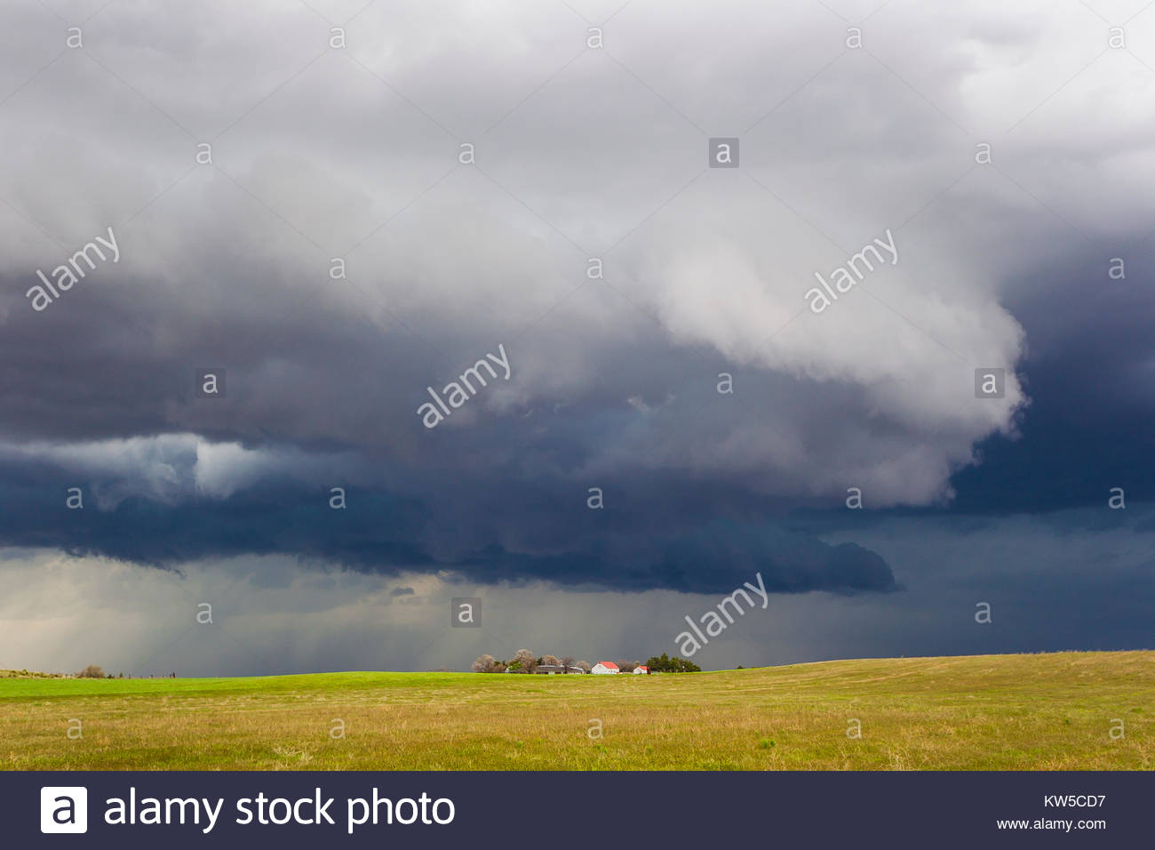 A supercell thunderstorm developing over a farm house in Nebraska. - Stock Image