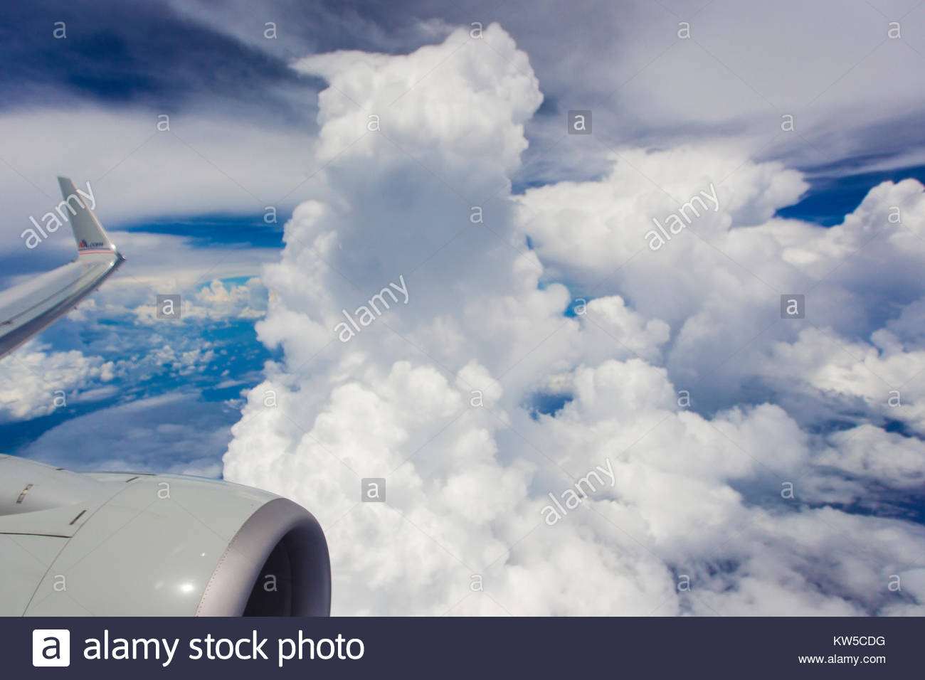 Cumulous cloud shooting up into the atmosphere, seen from a passenger airplane window. - Stock Image