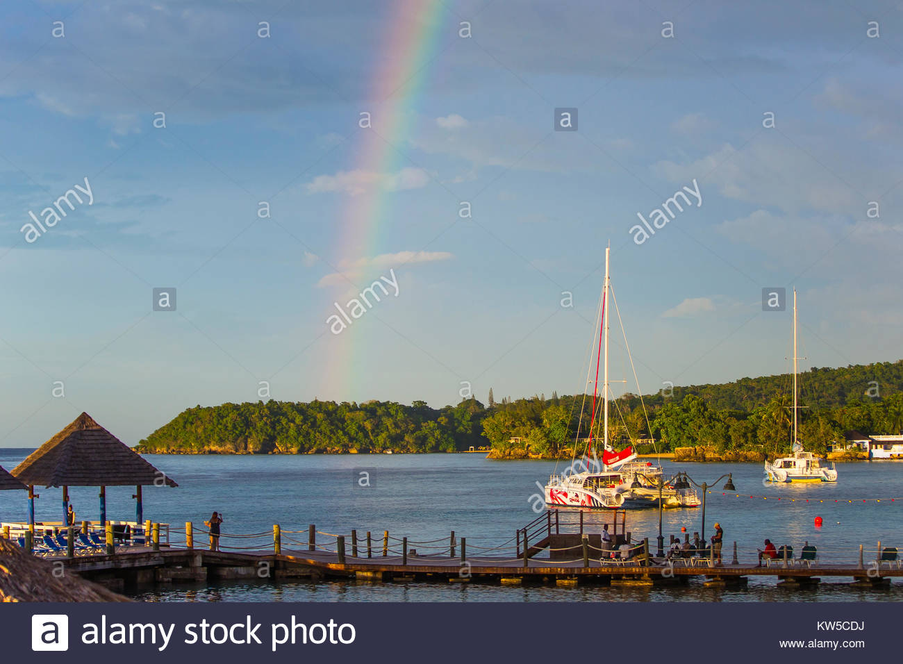 A rainbow over the water and shore in Ocho Rios, Jamaica. - Stock Image