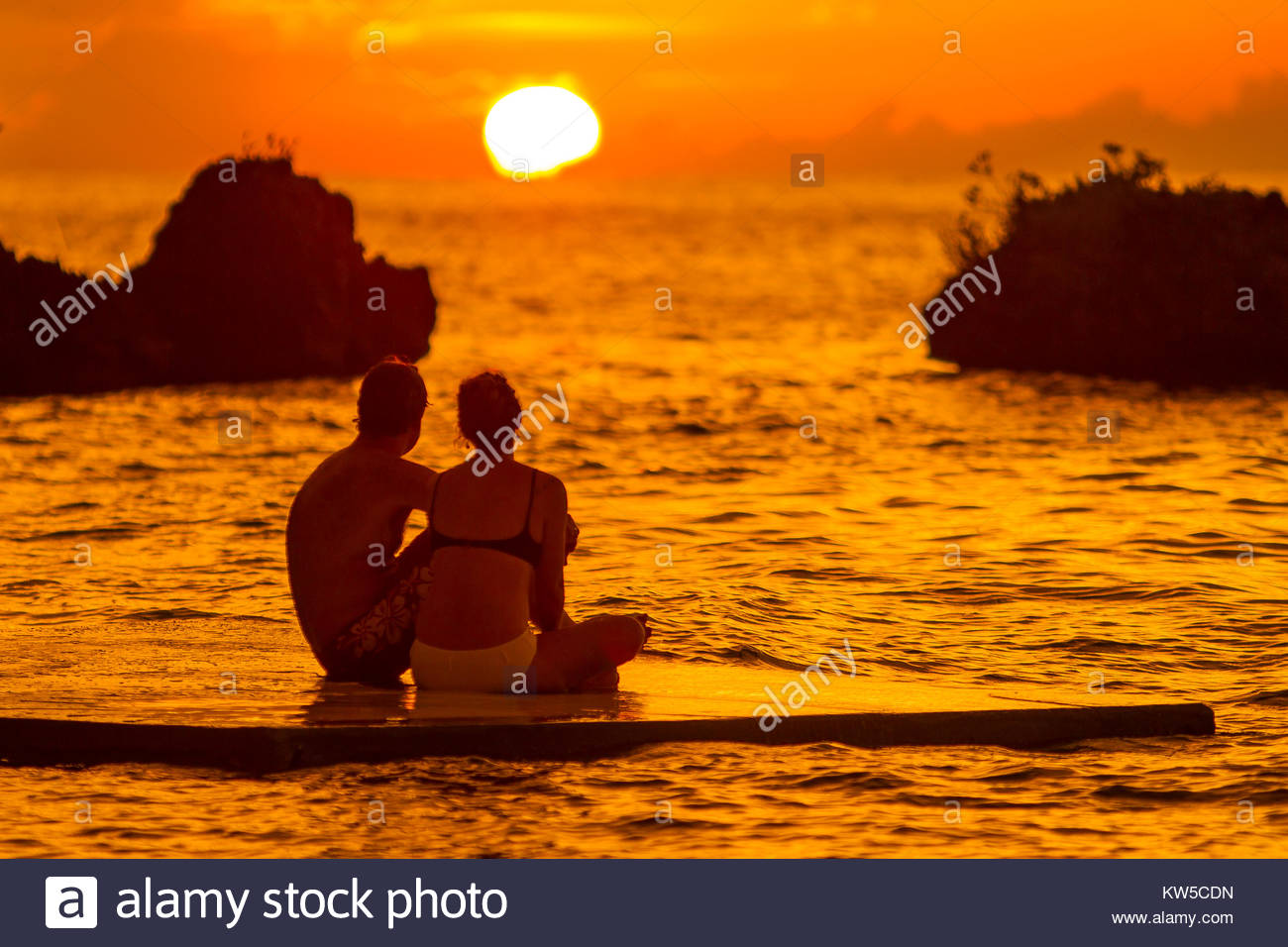 A silhouetted couple watch a romantic sunset from a floating dock in Ocho Rios, Jamaica. - Stock Image