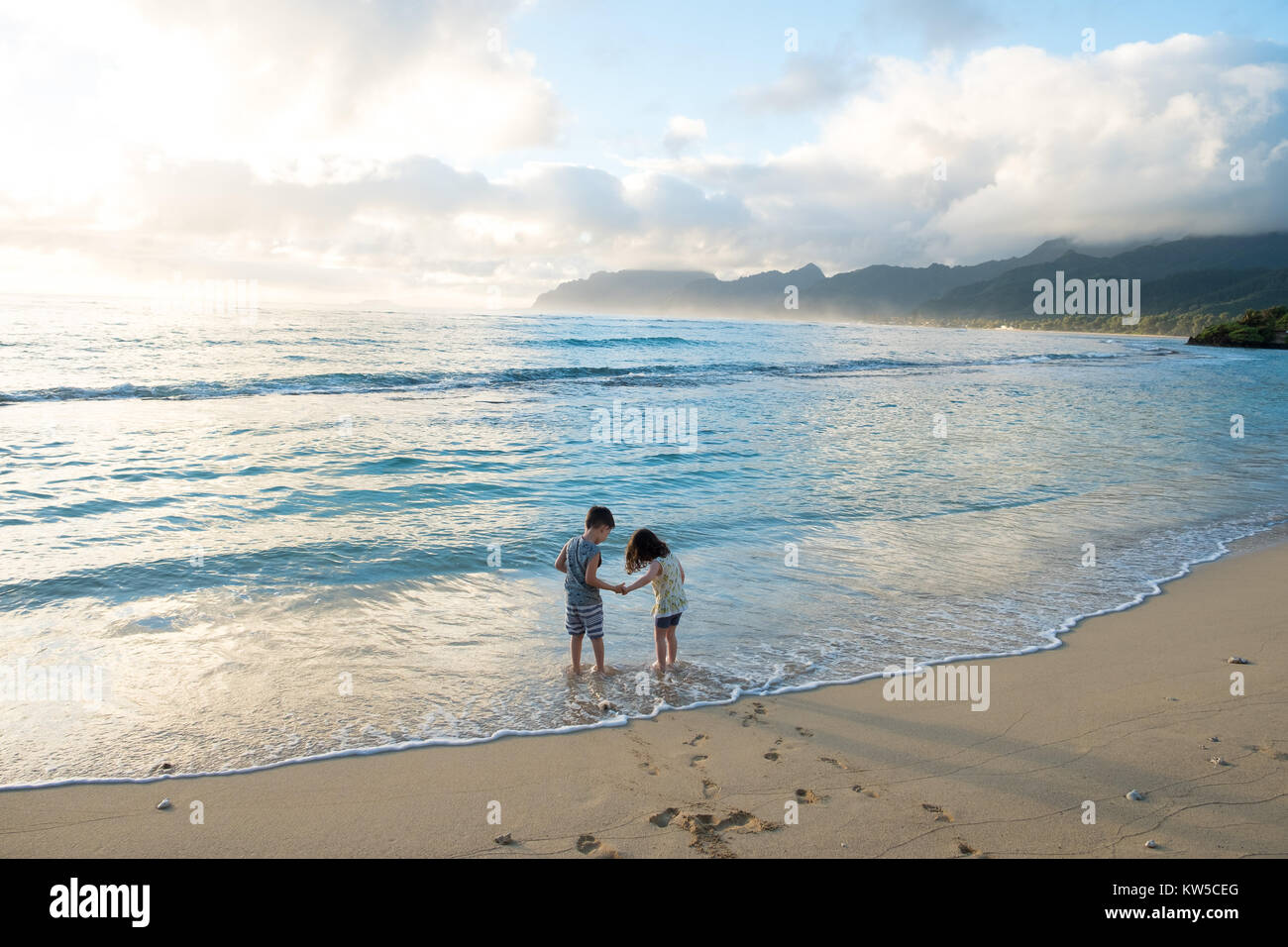 Siblings experiencing the beach and ocean together while on a tropical vacation to Oahu Hawaii with nice warm weather Stock Photo