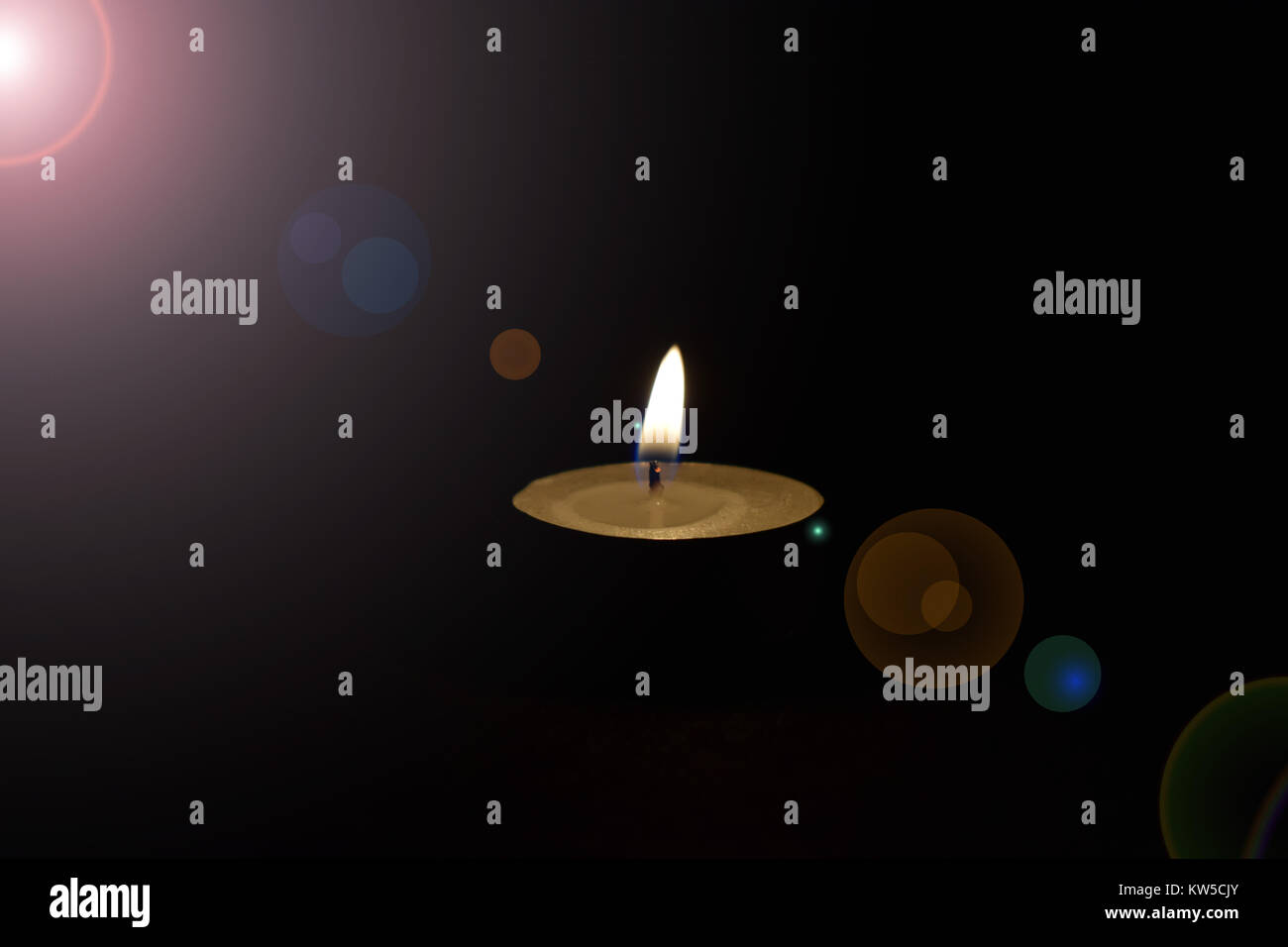 centered candle light on the black background with lens flare - Stock Image
