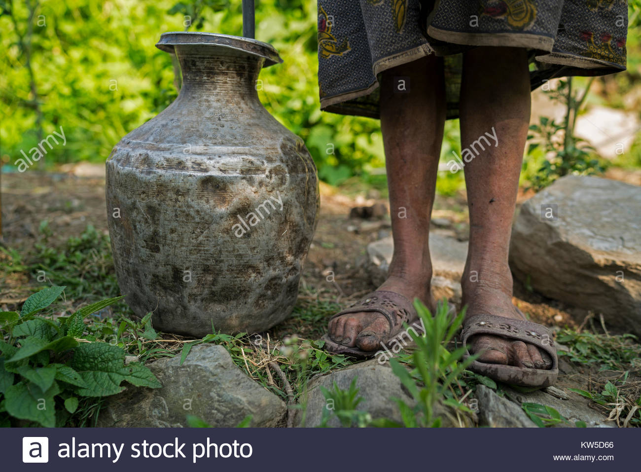 A person stands next to a metal container. - Stock Image