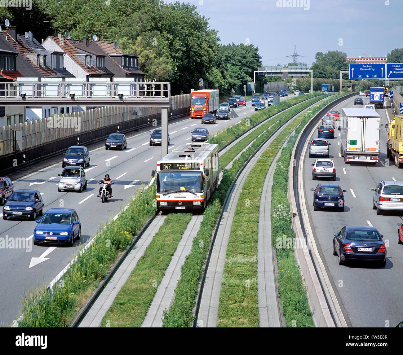 An O-Bahn 'guided bus' in its concrete guideway in the middle of a dual carriageway road, Essen, Germany. - Stock Image