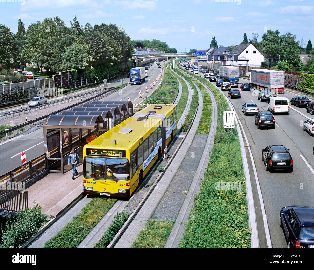 A passenger gets off an O-Bahn 'guided bus' on the outskirts of Essen, Germany. - Stock Image